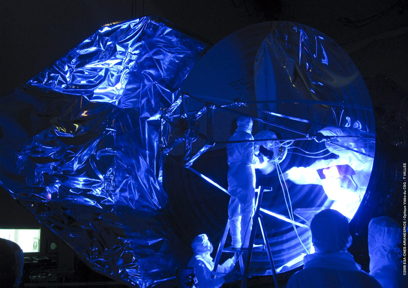 Herschel's 3.5-meter-diameter mirror is checked using ultraviolet light in the S1B clean room at Europe's Spaceport