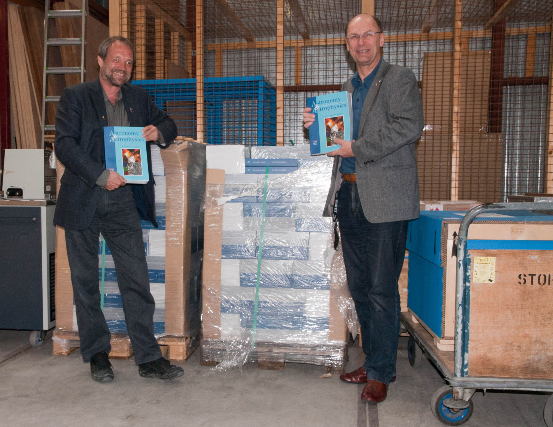 Johannes Riedinger and Göran Pilbratt stand in front of the Herschel A&A special issue supply in ESTEC Stores